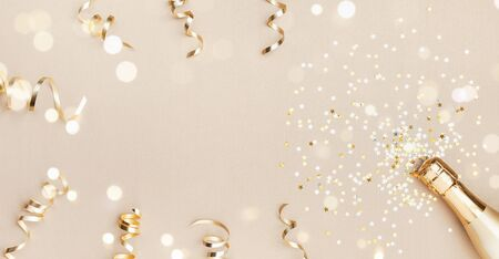 Champagne bottle with confetti stars, bokeh decoration and party streamers on golden background. Christmas, birthday or wedding concept. Flat lay. Imagens - 130489596