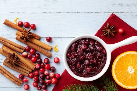 Cranberry sauce in ceramic saucepan with ingredients for cooking decorated with fir tree for Christmas or Thanksgiving day on rustic wooden table top view. Imagens - 130489669