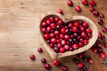 Cranberry in wooden bowl on rustic table top view. Imagens - 130489705