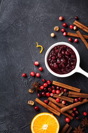 Cranberry sauce in ceramic saucepan with ingredients for cooking on stone black table top view.