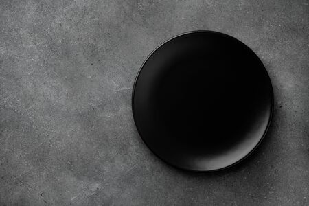 Black plate on dark stone table top view. Empty space for menu or recipe. Imagens