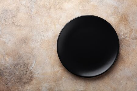 Black plate on stone table top view. Empty space for menu or recipe.
