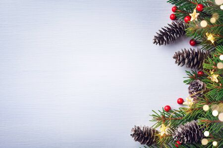 Christmas card. Fir tree branches with cones, red berries and light garland on white background. Top view with space for text. 写真素材