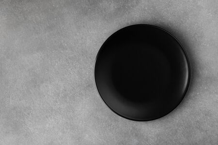 Black plate on gray stone table top view. Empty space for menu or recipe.