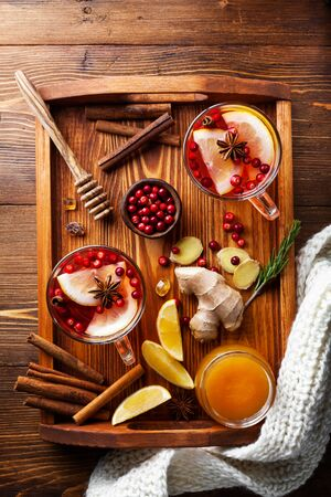 Healing cranberry tea in glass mugs in scarf with lemon, honey, ginger and spices. Autumn hot drink on rustic table top view. Фото со стока
