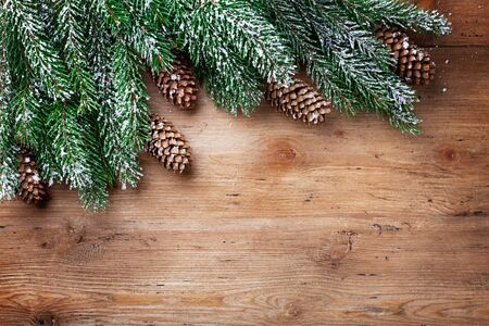 Christmas background. Snowy fir tree branches with fir cones on wooden board. Top view with space for text.