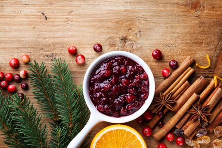 Cranberry sauce in ceramic saucepan with ingredients for cooking decorated with fir tree for Christmas or Thanksgiving day on wooden kitchen table. Top view.