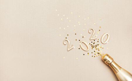 Creatieve kerst- en nieuwjaarssamenstelling met gouden champagnefles, confetti-sterren en 2020-nummers. Plat leggen. Stockfoto