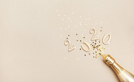 Creative Christmas and New Year composition with golden champagne bottle, confetti stars and 2020 numbers. Flat lay. Stock Photo