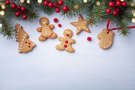 Christmas gingerbread cookies and fir tree on white background top view. Homemade sweet pastries for winter holidays.