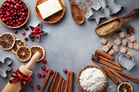 Bakery background with ingredients for cooking Christmas baking. Flour, brown sugar, butter, cranberry and spices top view.