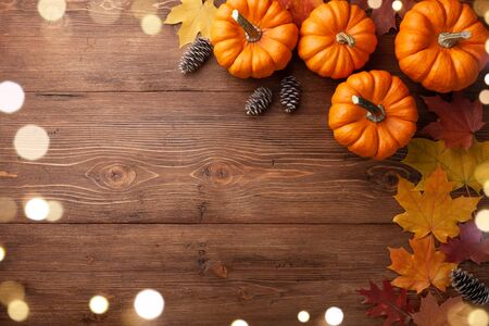 Autumn Thanksgiving background. Pumpkins and leaves on wooden table top view.