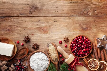 Bakery background with ingredients for cooking Christmas baking. Flour, brown sugar, butter, cranberry and spices on wooden table top view.