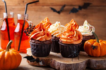 Halloween cupcakes and pumpkins on wooden background. Sweets for holiday party. Imagens - 131241154