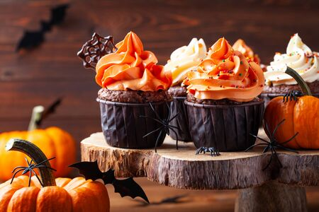 Halloween cupcakes and pumpkins on dark background. Sweets for holiday party. Imagens