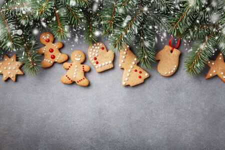 Christmas gingerbread cookies and fir tree with cones from above. Homemade sweet pastries for winter holidays. Snow effect background.