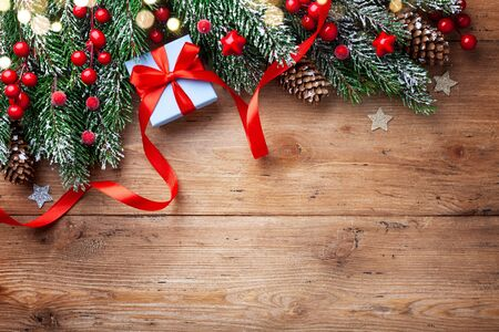 Christmas background. Snowy fir tree branches with fir cones, red berries and gift box with ribbon on wooden board. Top view with space for text. 写真素材