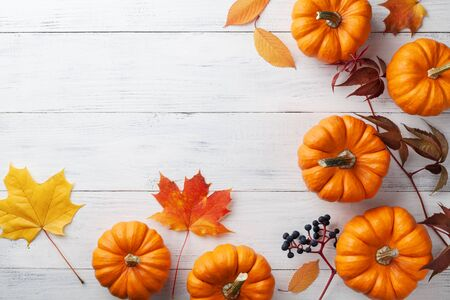 Autumn Thanksgiving background. Pumpkins and leaves on white table top view. Imagens - 131455932