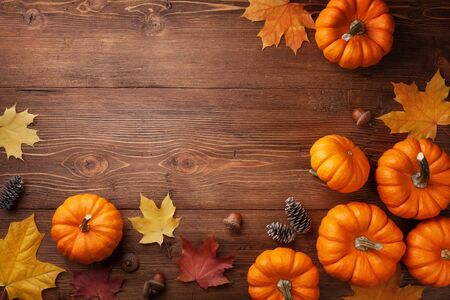Autumn Thanksgiving background. Pumpkins, acorns and leaves on wooden board top view. Imagens - 131457545