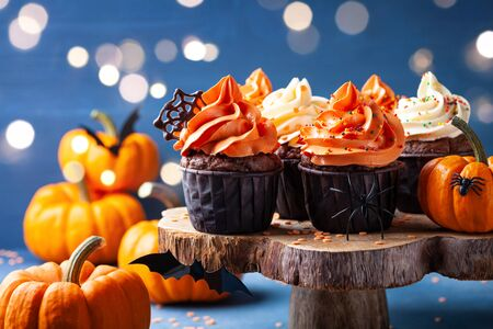 Halloween cupcakes and pumpkins on dark blue background. Sweets for holiday party. Imagens - 131456652