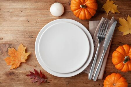 Autumn Thanksgiving table setting for dinner with plate, knife, fork decorated pumpkins and maple leaves. Top view.