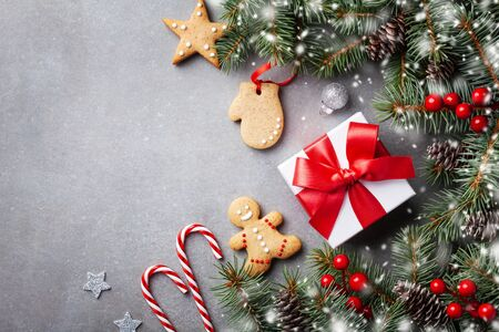 Christmas winter background. Gingerbread cookies, gift or present box and snowy fir tree top view. Imagens - 131456582