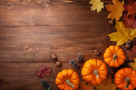 Autumn Thanksgiving background. Pumpkins, acorns and leaves on rustic table top view. Imagens - 131456929