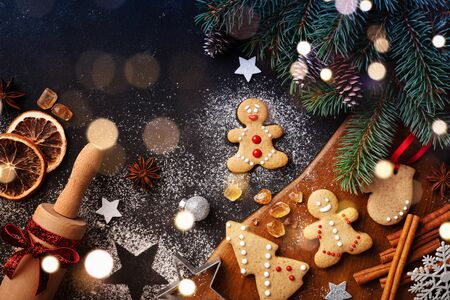 Christmas baking background. Gingerbread cookies, rolling pin and fir tree top view. Homemade pastries for winter holidays.