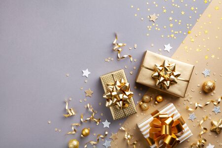 Golden gift or present boxes with golden bows and confetti top view. Christmas background. Flat lay style. Imagens - 131456673