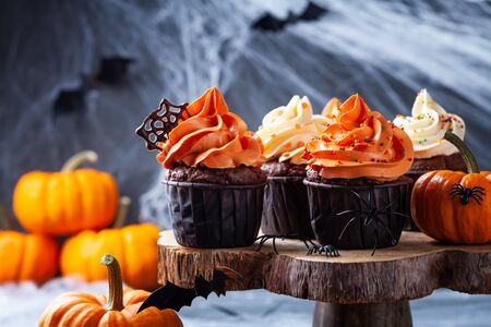Halloween cupcakes and pumpkins on dark web background. Sweets for holiday party.