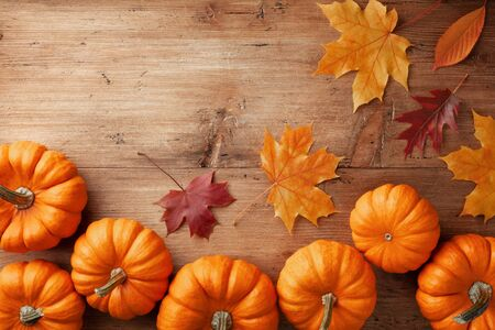 Autumn Thanksgiving background. Pumpkins and leaves on wooden rustic table top view.
