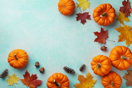 Autumn Thanksgiving background. Pumpkins and maple leaves on turquoise table top view. Imagens - 131456670