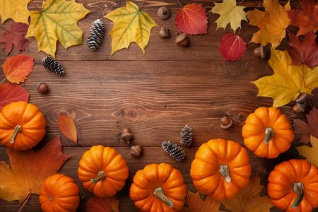 Autumn Thanksgiving background. Pumpkins, acorns and leaves on wooden table top view. Imagens - 131457037