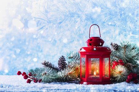 Christmas lantern in snow with fir tree branch. Winter cozy scene. Imagens - 131472122