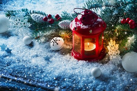Red Christmas lantern in snow with fir tree branch. Winter cozy scene.