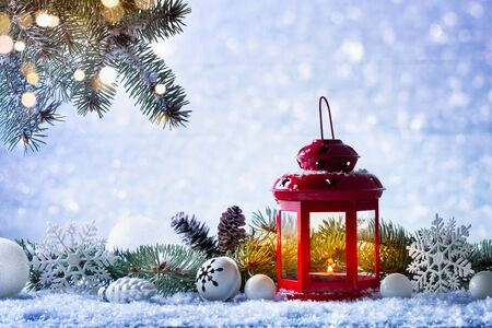 Christmas lantern in snow with fir tree branch and holiday decorations. Winter cozy scene. Imagens