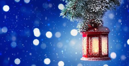 Christmas lantern hanging on snow covered fir branches. Winter cozy scene. Banner format.