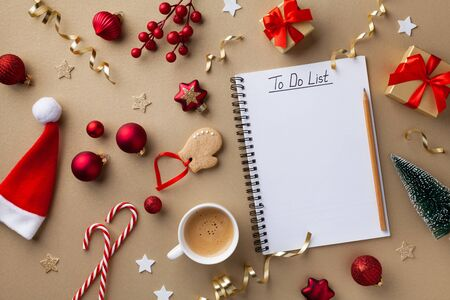 Cup of coffee, holiday decorations and notebook with to do list on golden background top view, Christmas planning concept. Flat lay style.