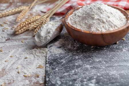 Wooden bowl of wheat flour and scoop on kitchen table. Ingredient for baking.