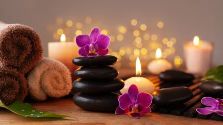 Spa, beauty treatment and wellness background with massage stone, orchid flowers, towels and burning candles. Archivio Fotografico