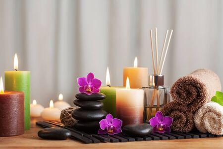 Aromatherapy, spa, beauty treatment and wellness background with massage stone, orchid flowers, towels and burning candles.