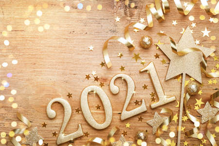 New Year celebration and festive background with golden numbers 2021, confetti stars and Christmas decorations top view.