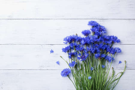 Bunch of blue cornflowers on white wooden table top view. Stock Photo