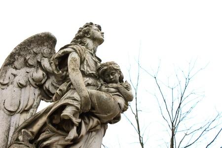 angel de la guarda: Escultura de un ángel con un niño Foto de archivo