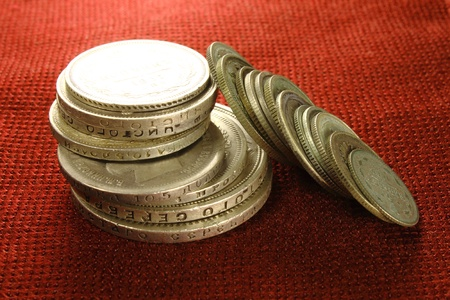 Silver antique coins on a red background