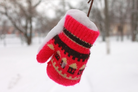 Red mitten in the snow in winter