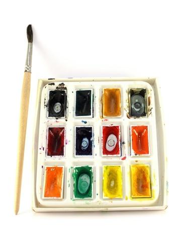 coloured paint and paintbrush on white background photo