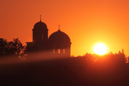 Silhouette of churches on a red sky and the sun photo