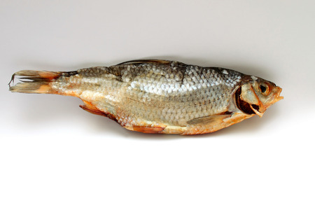 Dry fish on white background closeup photo