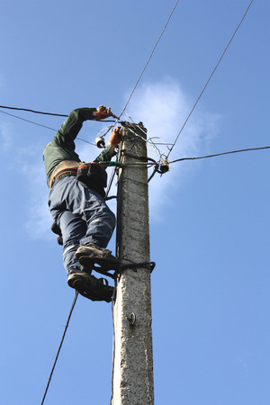 Electrician working on electric power pole photo